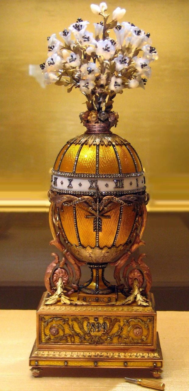 """Egg - watch """"Bouquet of lilies."""" Egg decorated with yellow transparent enamel on a guilloche pattern background and overlaid with colored gold, crowned with a bouquet of white lilies made of chalcedony and gold.  This is an Easter egg, made in the shape of antique French clock in the style of Louis XVI, is a kind of materialized recognition of Nicholas II of love to his wife."""