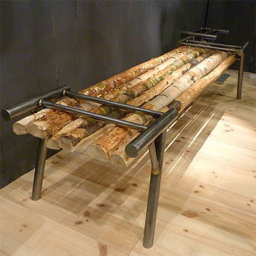A bench by Fredrik Karlsson. The two metal structures at either end hold the wooden branches in place for the goats to play on and chew – once they are chewed through, they are replaced. Part of the Greenhouse show at Stockholm Furniture Fair.