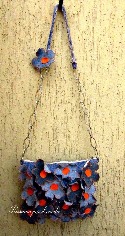 Voglia di colore, di fiori, di primavera questa borsa a tracolla gli racchiude tutte in una. Rappresenta un spirito giovanile pieno di freschezza. Realizzata in jeans.I fiori sono rifiniti a zig-zag con filo arancione , il centro di esse è in maglia arancione. La fodera è in raso panna con un comodissima tasca.  Dimissioni: H21cm x L26cm la tracolla e lunga 105cm