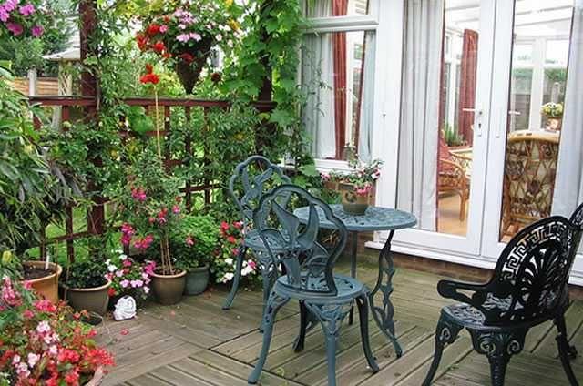 Terraço com flores e jogo de mesa e cadeiras de ferro