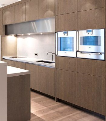 These Veneer Cabinets With No Handles, Waterfall Counter Tops, And Sleek  Plumbing Fixtures Give