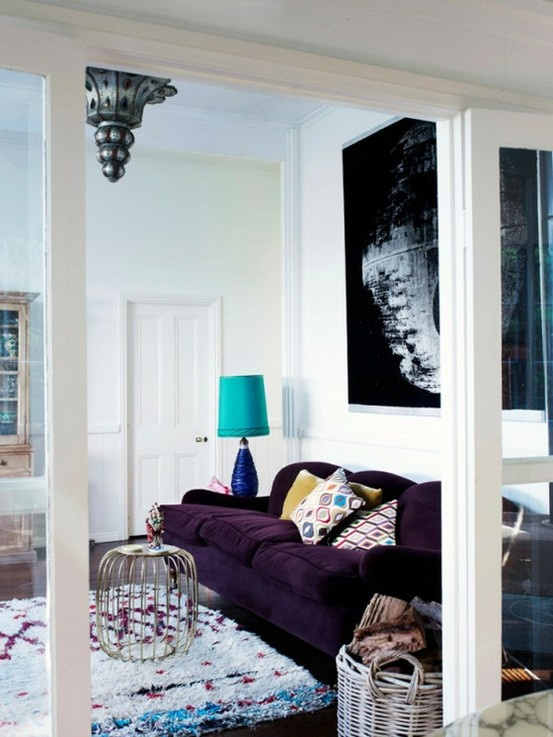 Colourful Living Room With White Walls, Blue Lamp, Colourful Tribal Rug,  Purple Velvet Sofa, Brass Table