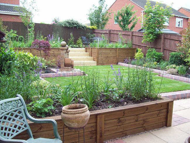 Two tier decked flower bed for the home garden for Small sloping garden designs