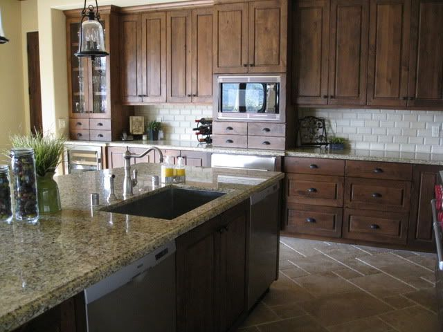 Dark stained knotty alder with granite help dark brown for Black and brown kitchen cabinets