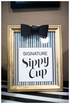 A signature sippy car bar for the guests of a first birthday party. Kids picked a sippy cup and fill it with their beverage of choice. A gold frame with a pin striped sign and bowtie detail.