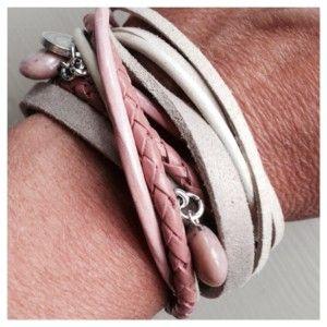 Wikkelarmband die  2x om de pols kan  van verschillende soorten leer. De armband heeft twee schuivers met bedels en een Cartierslot.