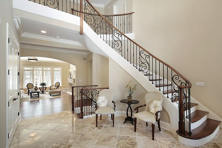 Foyer living room with wood stairs, wrought iron bannister, and elegant furniture