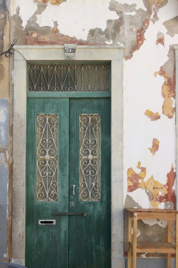 [Faro in 10 scatti] Porticine verdi coi riccioli e il muro che è un acquerello astratto.