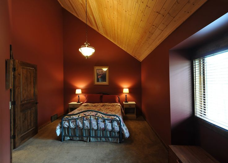 This country home has exciting decor with rustic door design, deep wall coloring and bright cedar tongue and groove ceiling.