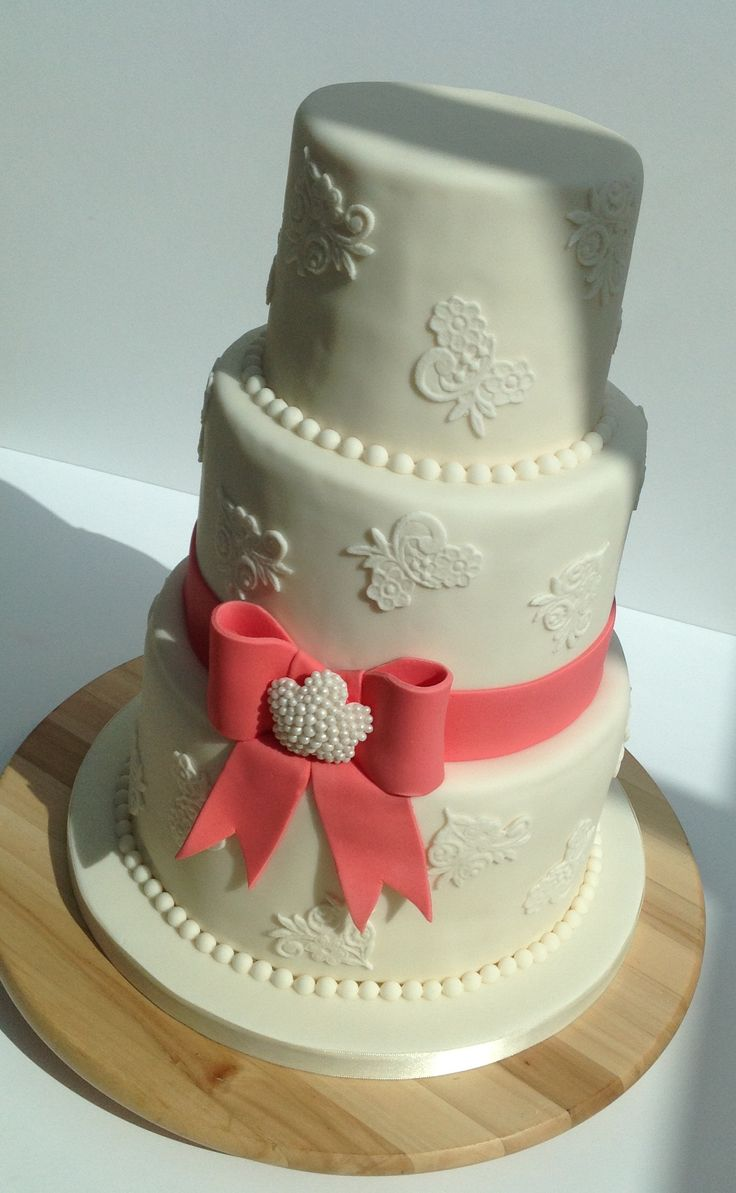 Ivory lace wedding cake with coral and pearl bow