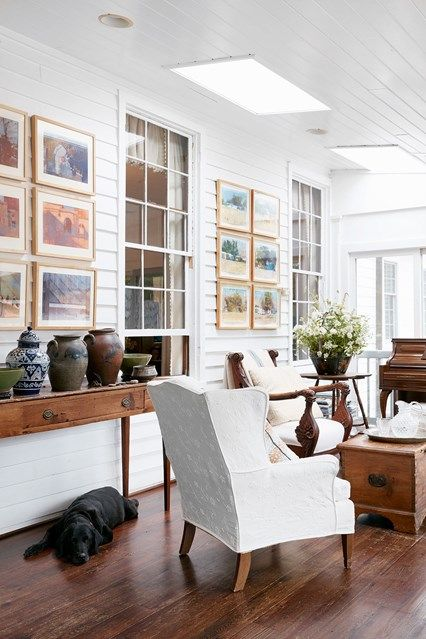 Panelled conservatory living room with white walls and dark wood floor, antique furniture and wooden framed artworks hung in grids.