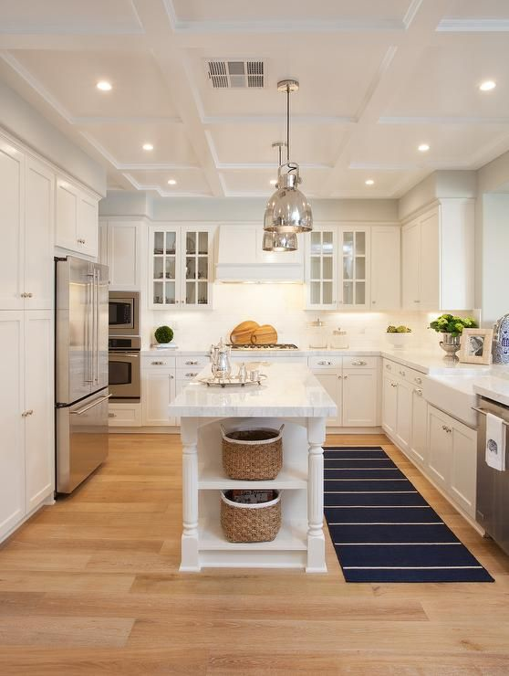 A pair of polished nickel industrial pendants hang over a narrow kitchen island with turned legs and shelves topped with white quartzite next to a navy striped runner.