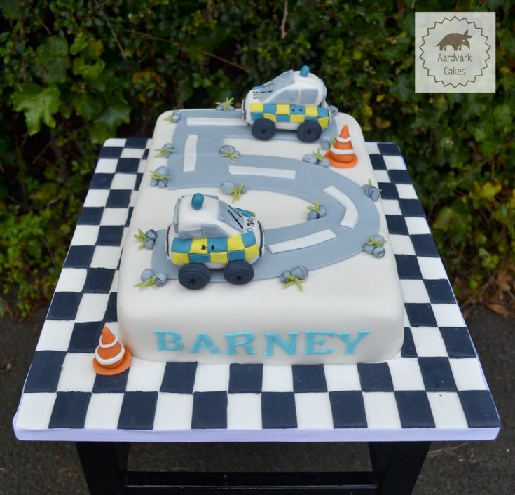 Police Car 5th Birthday Cake with chequerboard cake board and edible mini Police Cars
