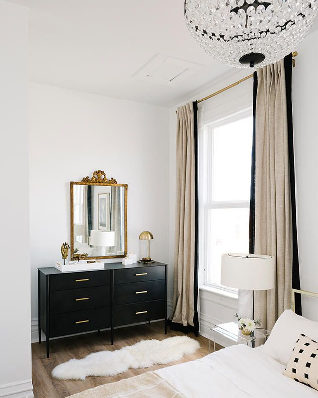 You need to see Havenly Head of Design Shelby Girard's black and white chic, modern home makeover—we love the airy and calming feel of this guest bedroom with it's white and blush bedding, antique gold mirror, crystal chandelier, sheepskin rug and glossy black dresser! Click to see more of this gorgeous renovation.