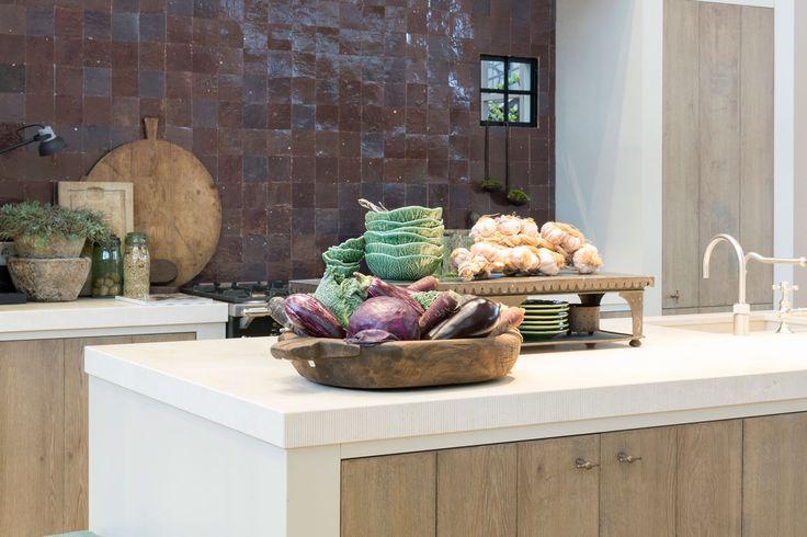 Mooie houten keuken van Tinello op Woonbeurs 2017 bij Wonen Landelijke Stijl. Aanrecht van natuursteen, eiken deurtjes en Frans zwart fornuis van Lacanche.