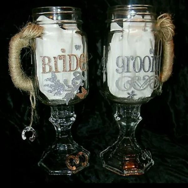 "New (never used) - His and Hers Mason Jars with Handles, Burlap /Jute Accents. 1-Set, Bride and Groom wedding mason jar burlap/jute toasting glasses. These two beautiful burlap and mason jars decorated with Jute , Horseshoes, beautiful Bride and Groom Accents. What a way to make a elaborate rustic statement on your wedding table with these Toasting Glasses. They could also be used as centerpieces as well! Names: Bride + Groom . They are pint mason jars with handles ""Homemade..."