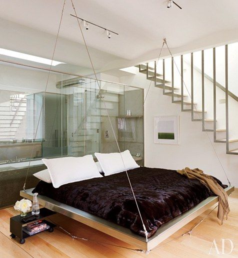 The master bedroom's floating bed is dressed in Calvin Klein linens, a mink coverlet by ER Fur Trading | archdigest.com