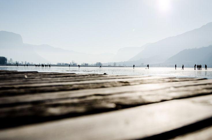 """Zugefroren ist er, der Kalterer See. Der Seerundweg verkürzt sich dadurch ungemein. Wir könnten anstatt rund um den See auf dem See die Runde wandern oder quer über den See spazieren. Die Schlagzeilen """"Gefährliches Eis"""" und """"Mann aus Kalterer See geborgen"""" noch im Kopf, wagen wir es trotz Hundertschaften, die sich heute hier am nicht … Eiswandern auf und rund um den gefrorenen Kalterer See weiterlesen →"""