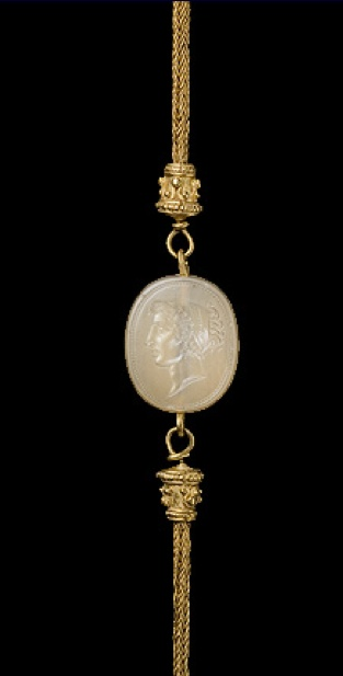 Gold chain of plaited wire with filigree and beaded terminals attached to a chalcedony intaglio head of a young woman, her wavy hair gathered up at the back, facing in profile towards the left within a cable border. Late 5th / 4th century B.C.