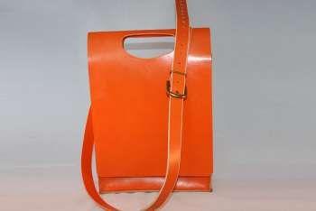Leren oranje tas  , gemaakt van tuigleer. De tas heeft een eigenwijs ontwerp en heeft een extra tasje voor kleine spulletjes en is voorzien van een sleutelkoord. De band is afneembaar en is in lengte verstelbaar. De afmetingen van de tas zijn ongeveer 27cm(B)x 38cm (H)x8cm (D). Door de beperkte beschikbaarheid van dit leer is dit een uniek exemplaar.