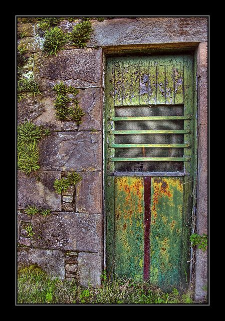 Porta de fazenda, antiga, ladeada por parede de pedras com musgo.  Fotografia: Farm Door via @Susan Caron Cohan.