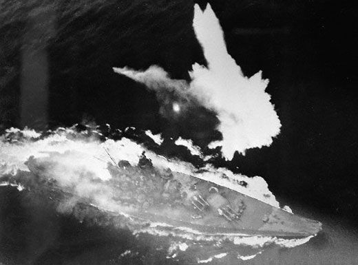 Yamato, the largest battleship in the world, under attack. A large fire burns aft of her superstructure and she is low in the water from torpedo damage. She was sunk in Operation Ten-Go, a suicide run M
