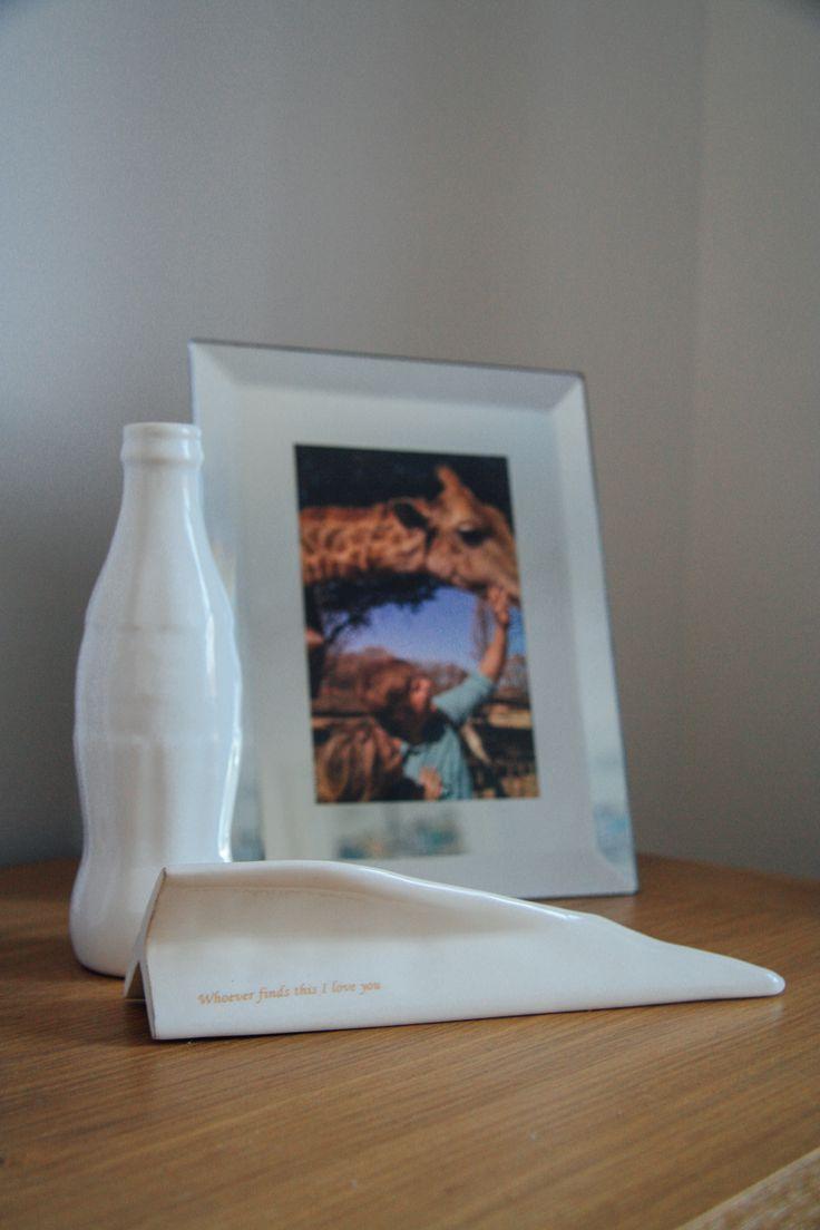 white ceramic paper plane and coke bottle