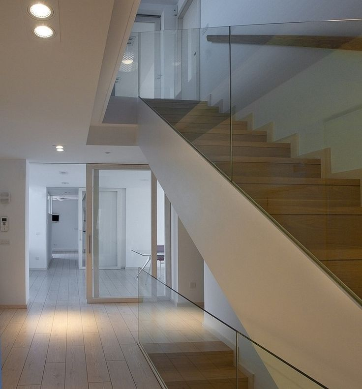 Bright hallway with white wooden floor and white wall design decorated by recessed ceiling lamps and sliding door also modern wooden staircase