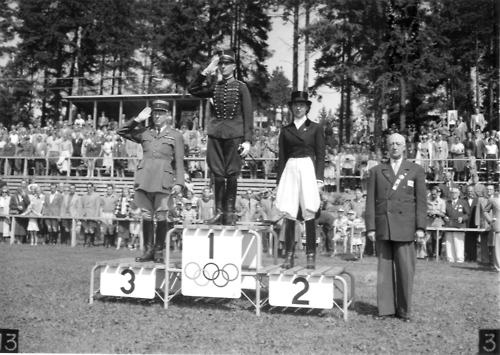 The 1952 individual Dressage podium – gold went to Henri St-Cyr (Sweden), silver to Lis Hartel (Denmark) and bronze to André Jousseaume (France). Women were first allowed to compete in Dressage in 1952, making Lis Hartel the first woman to medal in the sport. Eight years earlier Lis contracted polio while pregnant and became paralyzed from the knees down. Despite this impairment, Lis won silver medals in both the 1952 and 1956 Olympics.