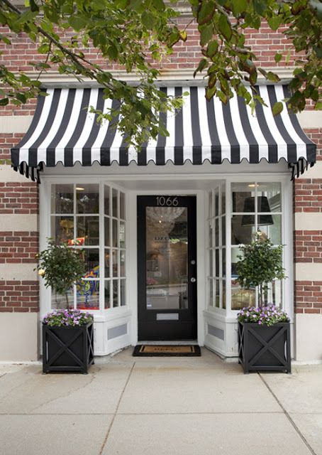striped awning, black windowed door with a mailslot, white trim, topiary bushes