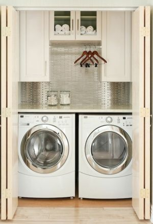 Side by side laundry closet with hanging rod and cabinets