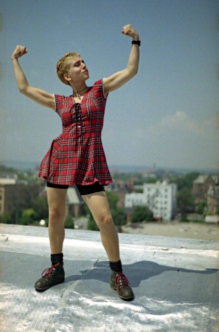Ani DiFranco poses on the roof of Buffalo's Sidway Buiding in a photograph that would become the iconic logo for Righteous Babe Records.