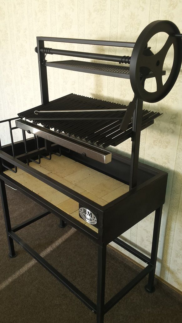 Argentine Grill with Side Brasero BM G-2 It'san ultimatewood/charcoal burning grill pit on the standfor home and small catering business use. These Argentine barbecue grills feature heavy duty black steel construction with a sidebrasero(embermaker) to make embers for authentic Argentine style cooking, and a traditional sloped Argentine style angle iron grill grate with adrippan.Argentine Grills …