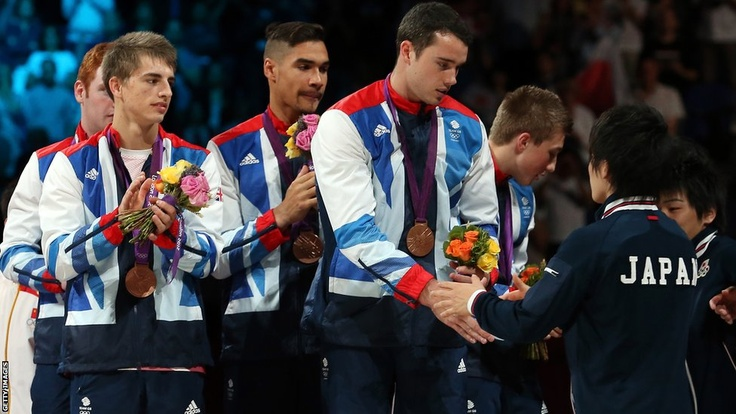 Bronze medalists Max Whitlock, Louis Smith, Kristian Thomas and Sam Oldham of Great Britain shake hands with Japan who won the silver, on the podium during the medal ceremony in the artistic gymnastics men's team final at North Greenwich Arena