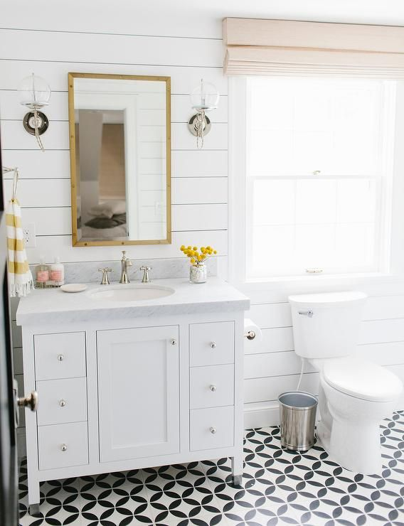 white and yellow bathroom features shiplap clad walls lined with a white washstand topped with carrera white bathroom tilesblack
