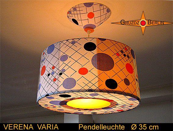 Leuchte VERENA VARIA Ø 35 cm, Pendellampe mit Diffusor und Baldachin. Eine Leuchte, bei der verschiedene  Materialen in Einklang gebracht wurden. Dem Retrostoff aus den 70er Jahren wurde teilweise blaues und orange farbenes Polypropylen unterlegt. So scheint die Leuchte in weiß orange und blau, wenn sie eingeschaltet wird. In der Mitte des Diffusors ist  orangefarbene Lichtfolie eingesetzt. So erinnert die eingeschaltete Lampe an ein Kaminfeuer.