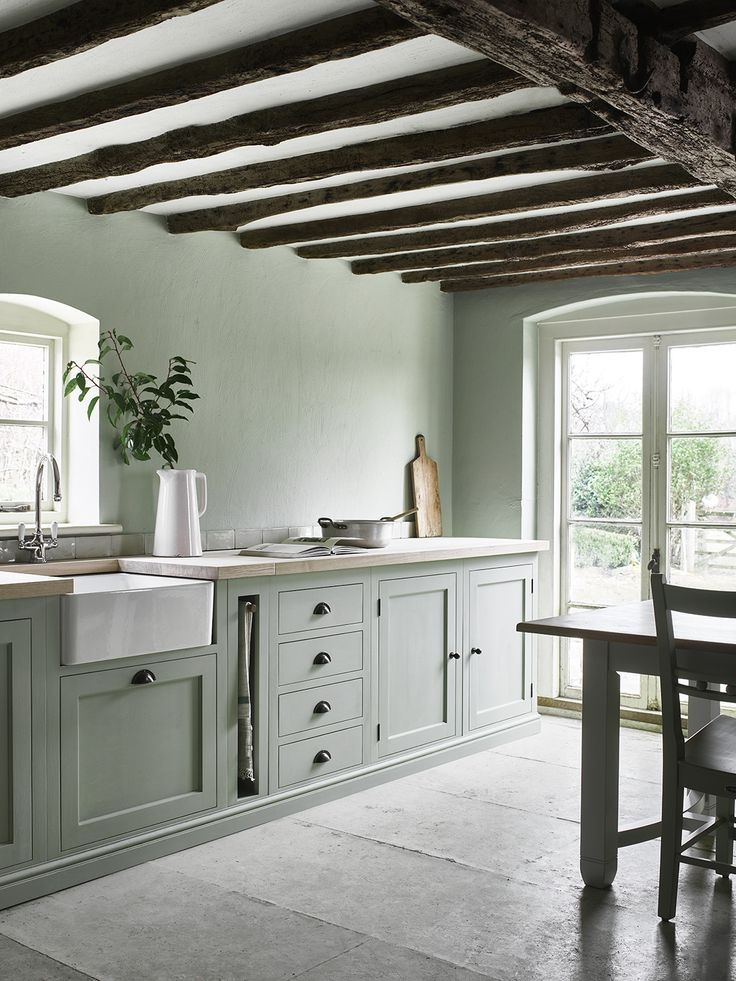 Neptune Henley kitchen hand-painted in Sage. Cottage beams. We ♥ green interiors!