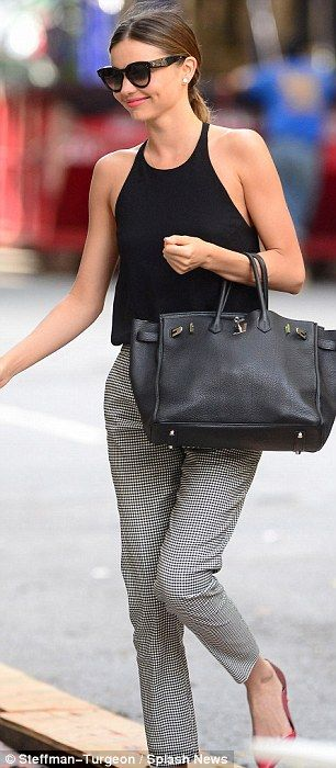 Back beauty: Model Miranda Kerr returns to her apartment on Friday after spending the nigh...