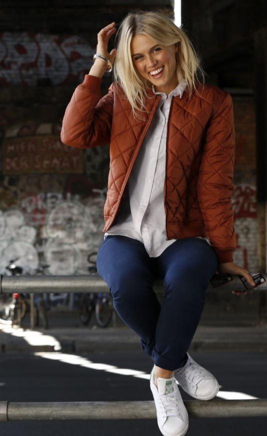 Die Bomberjacke in Rostorange hebt sich herrlich von den üblichen Grün- oder Schwarztönen ab – und ist ein cooles Basic für den Rest des Outfits: Eine Longbluse im Casual-Look, die klassische 5-Pocket-Jeans und die weiß-grünen Stan Smith. Dazu ein bisschen Metall und Glitzer als Accessoires.
