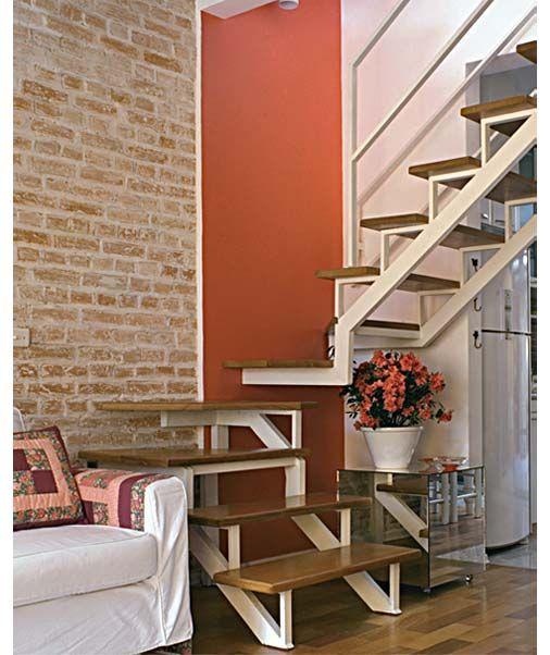 Uma das novidades da reforma desta casa foi a escada, agora vazada, que trouxe mais leveza ao ambiente. Os degraus de garapeira receberam uma resina que seca em três horas e não tem cheiro. O patamar fica entre a parede de tijolo aparente e a vibrante pintura vermelha, que foi inspirada num pedaço de tecido. Projeto de Fábia Mejorado Escobar.