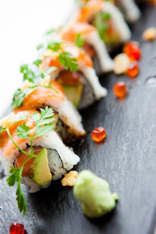 St. Barth Salmon Roll: Fresh Salmon, Avocado & Cream Cheese topped with Smoked Salmon served with a Micro Herb Salad, Ikura Caviar & Mango Dressing