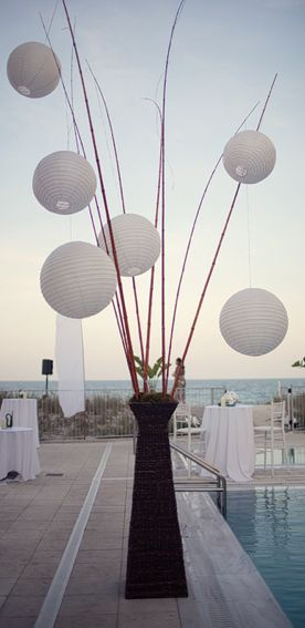 huge centerpiece white lanterns on dowels @Nicole Dyess I'm not totally in love with it, but something with height and continuing the lantern idea from upstairs for the gallery?