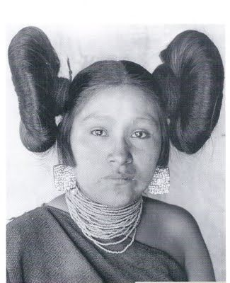 This is a photo of Hoo-n-ym-pka (Hopi) taken in 1901, wearing turquoise mosaic earrings and a necklace of glass seed beads strung with one larger bead, seen on the left. Her butterfly hairstyle is typical of postpubescent, unmarried Hopi women. Her manta is the traditional black woolen blanket dress worn by Pueblo women.