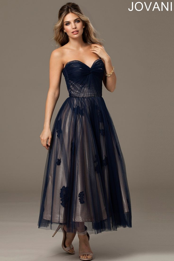 Ethereal loveliness is encapsulated in the adorable tea-length Jovani 92103 evening dress. This striking fit and flare gown features a filmy tulle overlay that is alluringly romantic. The strapless bodice has delicate ruching defining the bust area and showcases a sweetheart neckline, and semi-open back. The full skirt is gathered from the natural waistline and is accented with floral embellishments beneath the sheer tulle which extends beyond the natural hemline to create a charming tiered…
