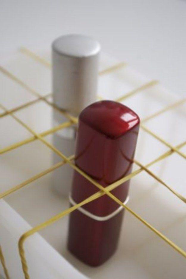 Para criar um organizador de batons, cruze elásticos em uma caixinha. | 26 ideias geniais para organizar seus itens de maquiagem