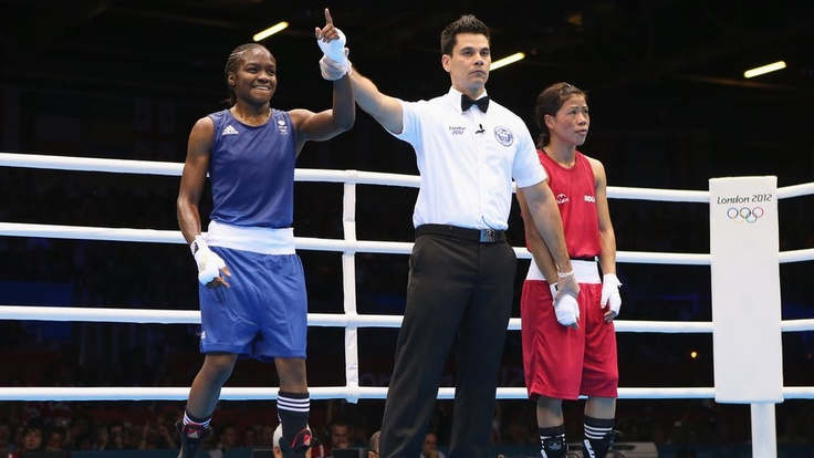 Great Britain's Nicola Adams becomes the first woman to win Olympic boxing gold with victory over China's Ren Cancan in the flyweight division.