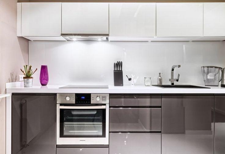 armoires de cuisine blanches et grises brillantes push-open et plan de travail en corian