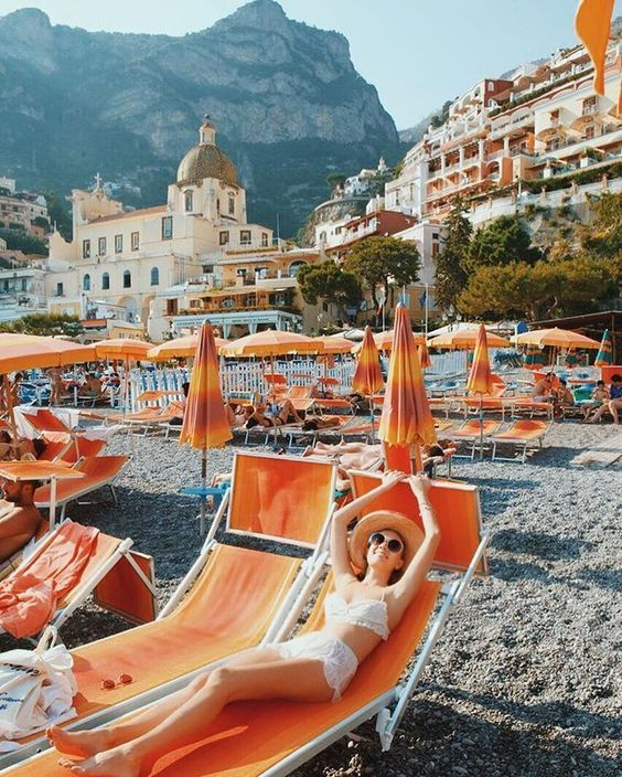 Girl lounging on orange chairs in Italy