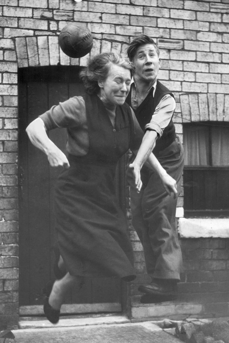 Manchester United midfielder Bobby Charlton practices his heading skills with his mother, Elizabeth, in the street outside their home, northern England, 1953, photographer unknown.