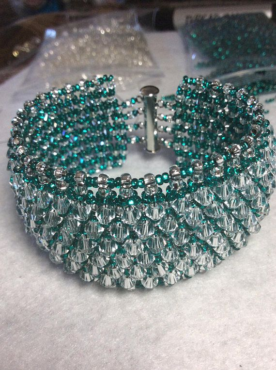 This classy piece will surely attract some attention If you like to stand out from the crowd this is an eye catcher Dark green seed beads for the netting they are surrounded by transparent crystal bicones which intensify the brilliance Closure is with sliding metal magnetic clasp